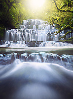The Purakaunui Falls are a cascading three-tiered waterfall on the Purakaunui River, in The Catlins of the southern South Island of New Zealand. As one of very few South Island waterfalls away from the alpine region, it has long been a popular destination and photographic subject.