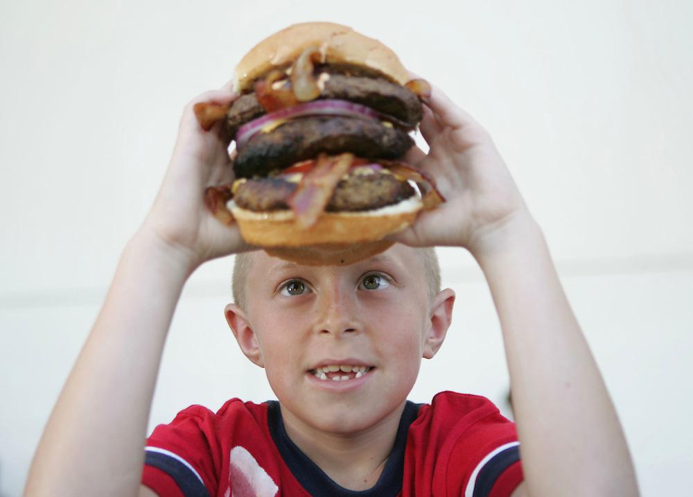 Sam Gerstein, 8, of Anaheim, eyes the Hucowamongous burger - 2.25 lbs of ground beef - at the 2007 Orange County Fair.