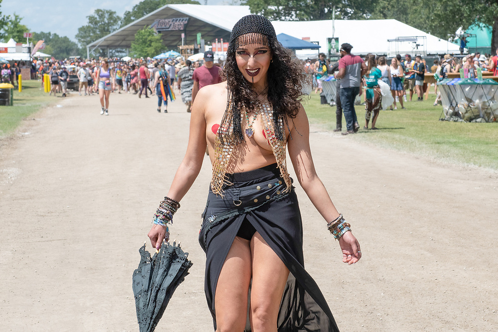 A young woman dressed as a belly dancer takes a stroll during The Bonnaroo Music and Arts Festival in Manchester, TN
