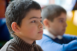 Portrait of boy looking serious during school assembly,