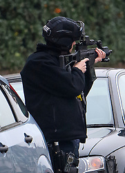 © Licensed to London News Pictures. 18/12/2016. London, UK. An armed police officer with his gun raised towards a window during an armed siege in Brixton, South London.  Police arrived after receiving reports of 'a man with a gun'. Photo credit: Ben Cawthra/LNP