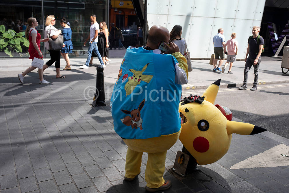 Pokemon Pikatchu who people pay to have their picture taken with makes a call on his mobile phone with his head removed in Chinatown, London, England, United Kingdom. Pikachu are a species of Pokemon, fictional creatures that appear in an assortment of video games, animated television shows and movies, trading card games, and comic books licensed by The Pokémon Company, a Japanese corporation.