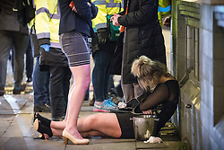 """© Licensed to London News Pictures . 19/12/2015 . Manchester , UK . A woman lies slouched on the pavement . Revellers in Manchester enjoy """" Mad Friday """" - also known as """" Black Eye Friday """" - the day on which emergency services in Britain are typically at their busiest , as people head out for parties and drinks to celebrate Christmas . Photo credit : Joel Goodman/LNP"""