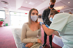 """© Licensed to London News Pictures. 10/07/2021. Sheffield, UK. Sophie Addison, 23, receives the first dose of the Pfizer/BioNTech vaccine at a pop-up vaccination clinic at Bramall Lane, home to Sheffield United football club in Sheffield, as part of the """"Grab a jab"""" campaign. Photo credit: Ioannis Alexopoulos/LNP"""