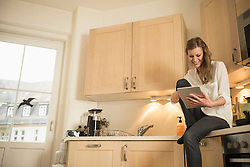 Young woman using digital tablet and sitting on kitchen worktop, Munich, Bavaria, Germany