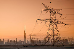 Electricity transmission lines and pylons and skyline  at dusk in Dubai United Arab Emirates