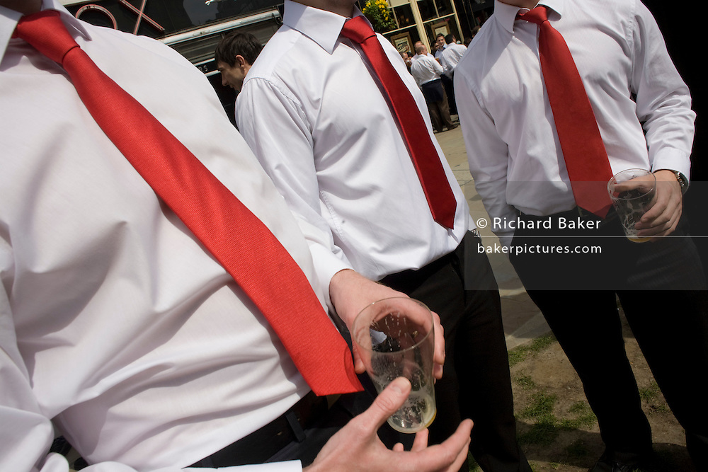 Holding drained pint beer glasses that symbolises an economic recession, City of London office workers gather to drink at lunchtime while dressed in red ties and white shirts, on the 23rd April, St George's Day, England's national day. In recent years, more English flags have become more prevalent in a resurgence of national pride and more citizens have come to work dressed with a red and white theme such as ties and shirts, hats or shoes. Anything for a little fun in such gloomy times. This anonymous trio have all agreed to dress identically and enjoy an early warm spell of good weather to show-off their dress sense and patriotism.
