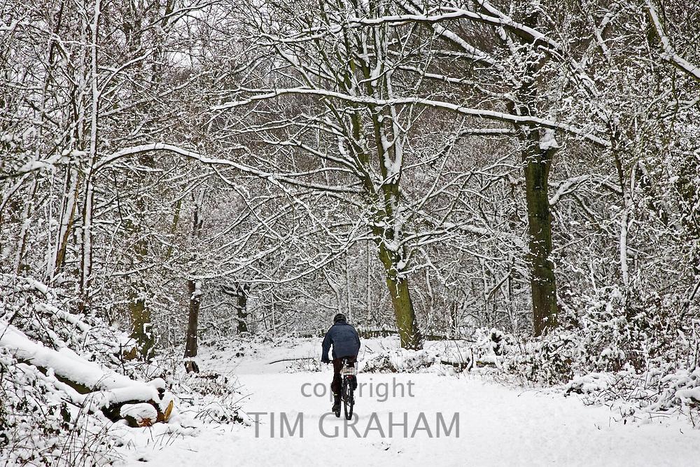 Man cycles across snow-covered Hampstead Heath, North London, United Kingdom