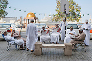 Omani taxi drivers reading newspapers on the Mutrah corniche in Muscat, the capital of the Sultanate of Oman.