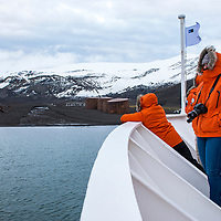 Guests on the bow of the National Geographic Explorer view the ruins of an old Norwegian whaling station inside of the caldera of Deception Island in Antarctica.