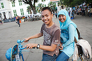 A young Indonesian couple riding a bicycle near the capitol square.<br /> Various scenes of the city of Jakarta in Indonesia.