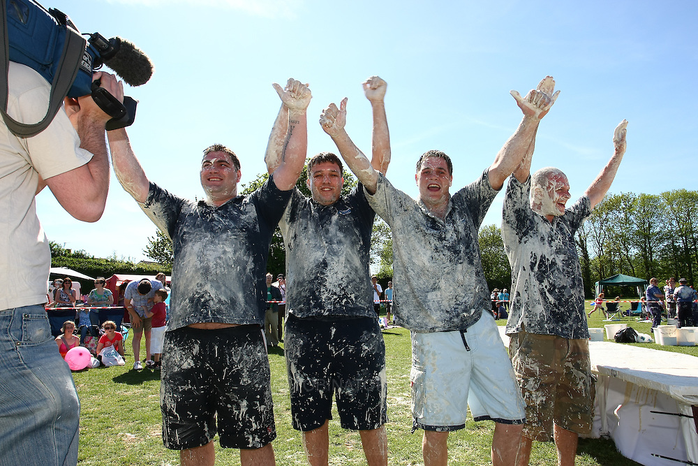 """Coxheath, Kent - Saturday, May 22nd 2010: Newly crowned world custard pie throwing champions """"The High Pressure Cleaning Comapny""""celebrate their win over the Coxheath team 96-56 at the World Custard Pie Championships at Coxheath near Maidstone, Kent. Left to right: Glen Draper (Maidstone), Karl Hickmott (Stockbury), Jimmy Hickmott (Stockbury), Terry Hadaway (Maidstone). The first championship was held in 1967 in Coxheath using a special custard recipe developed by Richard Hearn aka Mr Pastry. The championship is made up of teams competing in heats, semi finals and the final, with the number of pies available per team increasing from 5 in the heats to 10 in the final. 6 points are scored for a direct hit on the face, 3 points for the shoulders or upwards, 1 point for any other part of the body, and points are deducted for misses. A discretionary 5 points can be awarded for the most amusing and original throwing technique. The event is part of the Rotary Club funday. (Pic by Andrew Tobin/SLIK Images)"""