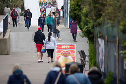 © Licensed to London News Pictures.  30/04/2021. Southend-on-Sea, UK. Member of the public walk along Thames Estuary in Southend-on-Sea, Essex. Forecasts predict chilly bank holiday weekend with showers which may turn heavy at times during the afternoon, most likely near the south coast. Photo credit: Marcin Nowak/LNP