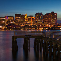 Scenic Boston Waterfront skyline photography featuring landmarks such as the Marriott Hotel or Custom House of Boston and One International Place photographed on a magnificent sunset night. <br />