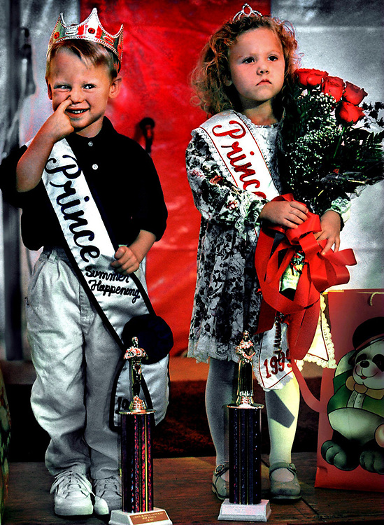 Three-year-old Brent Nakkula and four-year-old Brittany Price are presented to the crowd after their crowning ceremony as Wee Lad and Wee Miss of the Linden Summer Happening Festival. The two really didn't know what to think of their new found fame.