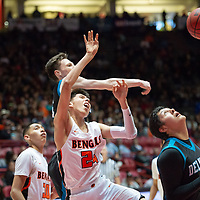 """Gallup Bengals Quinn Atazhoon (24) is blocked by Del Norte Knights Jordan Neilsen (23) in the paint during the NMAA State Tournament. The Knights defeated the Bengals 55-49 at """"The Pit"""" in Albuquerque Wednesday evening."""