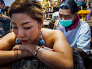 28 OCTOBER 2018 - BANGKOK, THAILAND: A woman gets a tattoo done by hand with a long needle, in the traditional Thai style, at the 2018 MBK Center Tattoo Fest. Tatoo artists from around the world came to participate in the festival, which featured both modern (using tattoo machines) and traditional methods (done by hand with long needles) of tattooing.    PHOTO BY JACK KURTZ