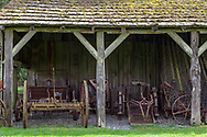 Old farm equipment at a storage area on the side of the Gable Roof Barn (1898) at the Annand Rowlatt Farmstead.  This farmland was first used by Joseph and Sarah Anne Annand and later by Len Rowlatt until his death in 1972.  The property is now part of Campbell Valley Regional Park in Langley, British Columbia, Canada.