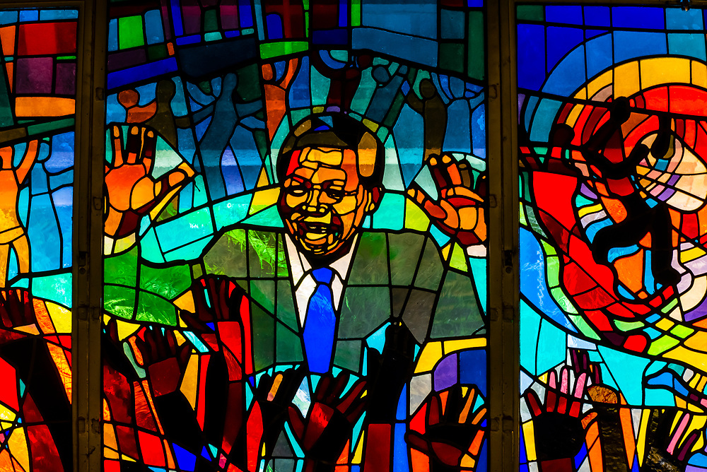 """Nelson Mandela stained glass window at Regina Mundi Church, Soweto, Johannesburg, South Africa. It is the largest Roman Catholic church in South Africa. Due to the role it played as a place of gathering for the people of Soweto in the years before, during, and after the anti-apartheid struggle, it is often referred to as """"the people's church"""" or """"the people's cathedral""""."""