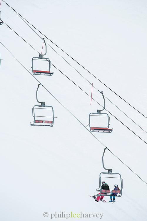 Two people on ski lift at ski resort, Nagano, Japan