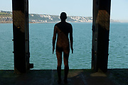 Public art sculpture by Antony Gormley in Folkestone, England, United Kingdom. This Antony Gormley cast iron figure is from the series 'Another Time' and is located on the half tide loading bay of the Folkestone Harbour Arm.