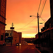 Vicksburg, Mississippi at dusk. This elegant historic town with its pillar fronted houses and cotton legacy  is transformed as the remains of a storm at sunset  turn the sky iridescent. There are perhaps defining moments on all big trips. Arriving in Vicksburg, Mississippi at dusk just as a  huge thunderstorm was beginning to break was one of them. It had been raining so hard, that an alligator had mistook the four-lane Interstate for the swollen Mississippi beside it and tragically met its death there. But as we drew into elegant Vicksburg, with its pillar-fronted houses on hilly streets, something astonishing happened. The sky, the result of a hot, setting sun, and the remains of a storm, was suddenly alive with an iridescent glow, so otherworldly, it looked like a space ship had landed. A rainbow stretched between two red brick towers, and you could just hear hear a steamer's horn, as it edged its way down the mighty Mississippi.