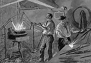 Welding a bicycle frame: France.  Frame suspended over forge and operator applies welding rod.  Wood engraving Paris 1896.