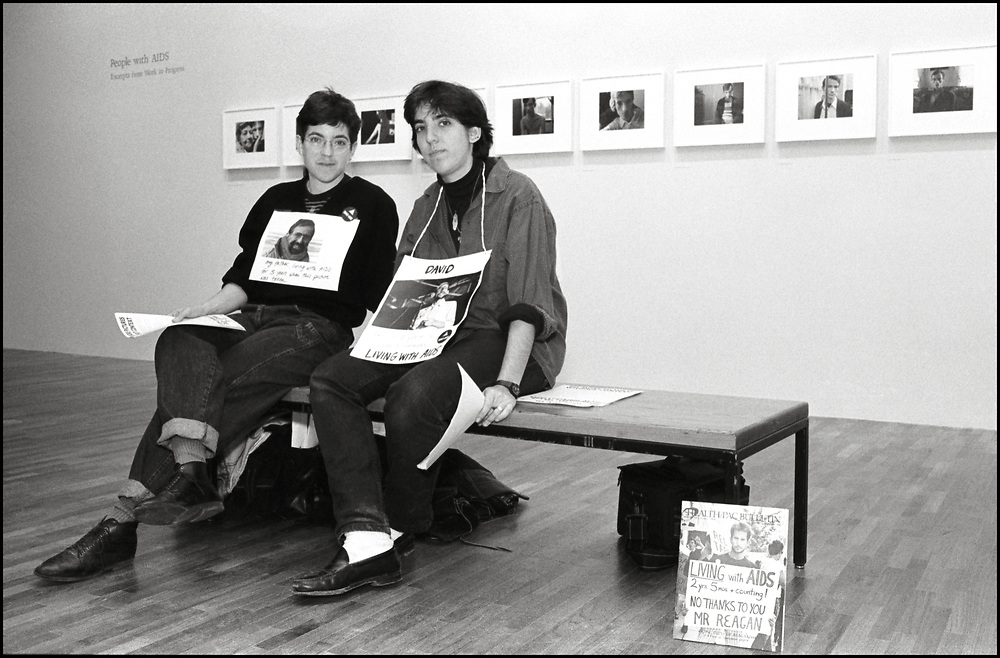 """At a 1988 MoMA exhibition of Nicholas Nixon's photographs of people with AIDS, activists from ACT UP (Alexis Danzig and Ellen Neipris pictured here) sat in the gallery with photographs of people captioned as """"living with"""" - not dying of - AIDS. The activists talked to viewers to offer an alternative perspective to the images of """"AIDS victims"""" and handed out flyers that called for """"no more pictures without context"""" and an end to photographs that displayed passive and ravaged individuals. It concluded with the demand """"Stop looking at us, start listening to us"""","""