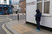 At the beginning of the second week of the UKs Coronavirus lockdown and in accordance with government guidelines for social distancing and the forced closure of all shops and local businesses, a hooded man wearing a surgical mask and gloves uses his phone on the corner of East Dulwich Grove SE22 in East Dulwich, Southwark, on 30th March 2020, in London.