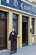Elderly woman strolls past O'Connells bar in Charleville, County Cork