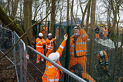 Steeple Claydon, UK. 23 February, 2021. Men in high-visibility clothing erect fencing and use a chainsaw to fell trees during an operation by National Eviction Team bailiffs acting on behalf of HS2 Ltd to evict activists opposed to the HS2 high-speed rail link from ancient woodland known as Poors Piece. The activists created the Poors Piece Conservation Project there in spring 2020 after having been invited to stay on the land by its owner, farmer Clive Higgins. Already, local village communities have been hugely impacted by HS2, with 550 acres of land seized including a large section of a nature reserve.