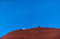 A Man sits atop a huge monolithic rock (as the moon sets behind) at the Red Rock Balloon Rally, Rock State Park, Gallup, New Mexico USA.