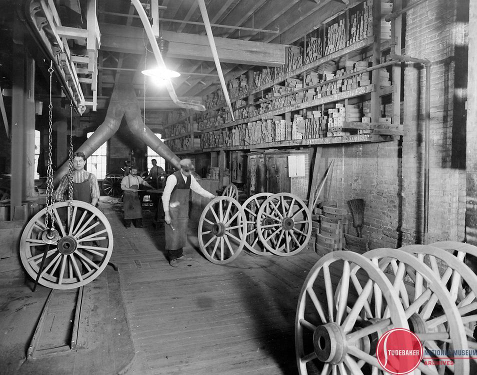 Studebaker workers prepare wagon wheels in this c. 1900 image.