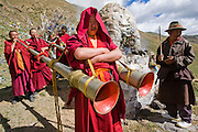 Monks blow horns as they prepare for prayer outside a monastery in the Tibetan Plateau.