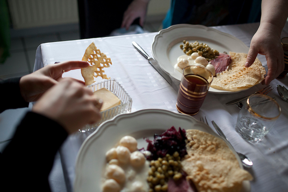 Nanna Rögnvaldardóttir sitting down to a simple but (mostly) traditional Christmas day meal of  smoked lamb, canned peas, laufabrauð (leaf bread) and spiced cabbage with her son Hjalti Nönnuson and daughter-in-law Þorbjörg Ágústsdóttir at her home in Reykjavik, Iceland, December 25, 2013.