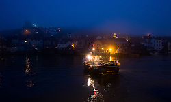 © Licensed to London News Pictures. 03/04/2014<br /> <br /> Whitby, North Yorkshire, United Kingdom<br /> <br /> Fishermen are illuminated by spot lights on their boat as they head out to sea to check their lobster and crab pots as heavy fog shrouds the harbour in the North Yorkshire seaside town of Whitby. <br /> <br /> Photo credit : Ian Forsyth/LNP