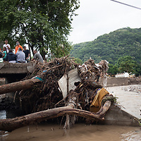 Pastor Julio Caballero (orange shirt) stands with local inhabitants on the broken bridge at El Calan, washed away and covered by debris with the flooding from hurricanes Eta and Iota.