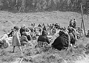 """9305-B7362-2. Indians play the stick game at Celilo village during the annual Feast of the First Salmon on April 7, 1940. This is the traditional way of playing stick game, no drums or anything to make noise. Girl standing at left is Ella Jim (wife of Nathan """"8-Ball"""" Jim) Woman in center is Alice Wahnuhie Minninick. Photo was published in the Oregon Journal on 12 May 1940,"""