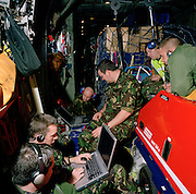 Members of the the elite 'Red Arrows', Britain's prestigious Royal Air Force aerobatic team, spend hours aboard a C-130 Hercules transport aircraft during a two-day journey from RAF Scampton to RAF Akrotiri, Cyprus. The interior is basic with sharp corners but the walls are padded.  Ward wears a heavy camouflaged coat to counteract the cold and ear-plugs from the droning engines. The Red Arrows pilots fly their Hawk jet aircraft to air shows but on long journeys requiring the support of ground crew borrow RAF transporters that fly behind the main airborne squadron shipping 10 tons of spares and personal effects for their six-week winter training stay.