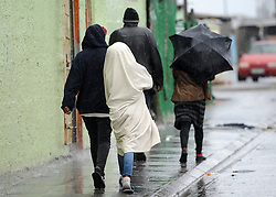 Cape Town - 180630 - People huddle togetheras they move from place to place taking shelter under blankets and umbrellas in Capricorn park Saturday - Photographer - Tracey Adams/African News