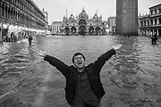 Venice, Italy. 29 October, 2018. A tourist enjoy the high tide in St. Mark square on October 29, 2018, in Venice, Italy. This is a selection of pictures of different areas of Venice that the press has not covered, were resident live and every year they have to struggle with the high tide. Due to the exceptional level of the 'acqua alta' or 'High Tide' that reached 156 cm today, Venetian schools and hospitals were closed by the authorities, and citizens were advised against leaving their homes. This level of High Tide has been reached in 1979. © Simone Padovani / Awakening / Alamy Live News
