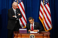 U.S. President Barack Obama signs the American Recovery and Reinvestment Plan as vice-president Joe Biden (L) looks on at the Denver Museum of Nature and Science in Denver February 17, 2009. Obama signed a $787 billion economic stimulus bill into law on Tuesday as global markets plunged on fears that the recession would deepen despite government action in many countries.  REUTERS/Rick Wilking (UNITED STATES)