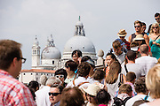 """Crowds of people near Saint Mark's Square, across from Basilica di Santa Maria della Salute. Venice (Venezia) is the capital of Italy's Veneto region, named for the ancient Veneti people from the 900s BC. The romantic """"City of Canals"""" stretches across 100+ small islands in the marshy Venetian Lagoon along the Adriatic Sea in northeast Italy, between the mouths of the Po and Piave Rivers. The Republic of Venice was a major maritime power during the Middle Ages and Renaissance, a staging area for the Crusades, and a major center of art and commerce (silk, grain and spice trade) from the 1200s to 1600s. The wealthy legacy of Venice stands today in a rich architecture combining Gothic, Byzantine, and Arab styles."""