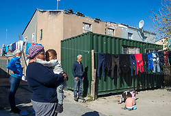 South Africa - Cape Town - 15 July 2020 - Margeret 'Auntie Maggie' Bruiners(pictured here with one of her grandchildren, Leandra and husband, John in the background) and her family of 8 have been living in a container for the past two years in Eastridge, Mitchells Plain. Her double story house, behind the container, suffered heavy damage after a fire broke out two years ago. Picture Courtney Africa/African News Agency(ANA)