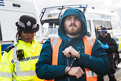 Colnbrook, UK. 27th September, 2021. Insulate Britain spokesperson Liam Norton is arrested after a slip road from the M25 at Junction 14 close to Heathrow is blocked by Insulate Britain as part of a campaign intended to push the UK government to make significant legislative change to start lowering emissions. The activists are demanding that the government immediately promises both to fully fund and ensure the insulation of all social housing in Britain by 2025 and to produce within four months a legally binding national plan to fully fund and ensure the full low-energy and low-carbon whole-house retrofit, with no externalised costs, of all homes in Britain by 2030.