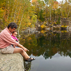 A man and his young daughter next to a pond on Millstone Hill in Barre, Vermont.  Abandoned granite quarry.  Fall. Millstone Trail Association.