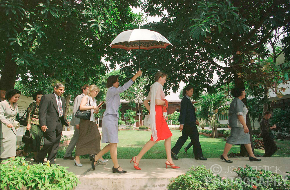 BANGKOK, THAILAND - FEB. 14, 2001 - Princess Mathilde of Belgium is escorted under cover of umbrella to a classrooom during a visit to the Protection and Occupational Development center Kredtrakarn of UNICEF, which provides shelter for women and girls who have benn victims of sexual exploitation. (Photo © Jock Fistick)