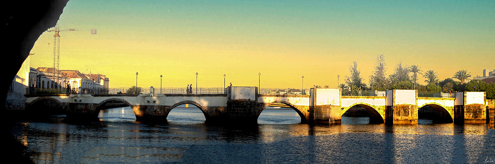 A view of the Roman Bridge in Tavira, Portugal at sunset.