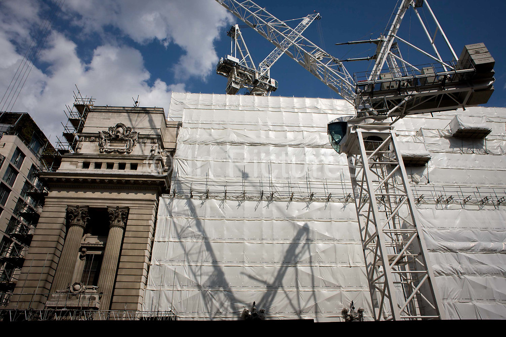 Shadow of a large crane on white sheeting covering City of London construction project. The pillars and columns of a Trinity Square building are partly protected by the sheeting. The building project is one of many changing the face of the City, the capital's financial quarter, its oldest part founded by the Romans in AD43. The City is a major business and financial centre. Throughout the 19th century, the City was perhaps the world's primary business centre, and it continues to be a major meeting point for businesses