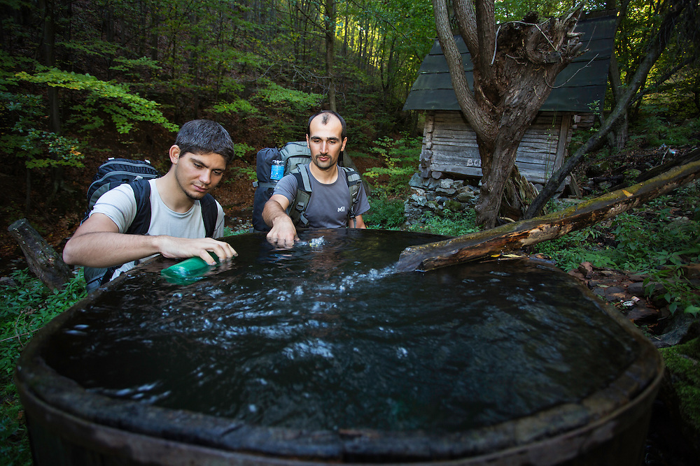Hikers (Adrian Grancea, left & Dan Dinu) replenishing their water supplies at an old mill in the forest outsde the village of Isverna. Geoparcul Platoul Mehedinți, Romania.